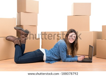 Beautiful girl with laptop and cardboard boxes unpacking in new home