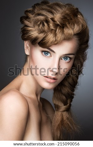 Beautiful girl with light make-up, perfect skin and hairstyle as a braid. Picture taken in the studio on a gray background