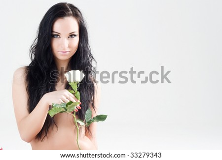 Beautiful girl with long black hair and white rose - stock photo