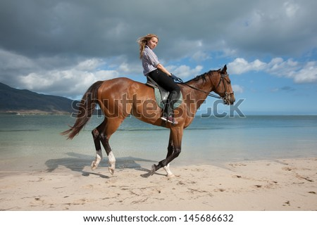 beautiful girl with long blond hair riding on a brown horse on the shore of Indian Ocean on the island of Mauritius - stock photo