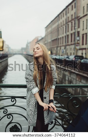 beautiful girl with long blonde straight hair with a coat and boots posing on the bridge over the river, cold weather, rain, sad mood, outdoor portrait, close up, - stock photo