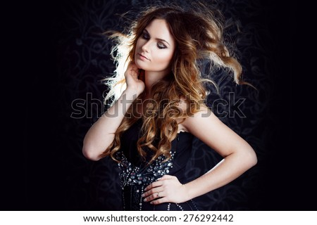 beautiful girl  with long brown curled hair, dark background - stock photo