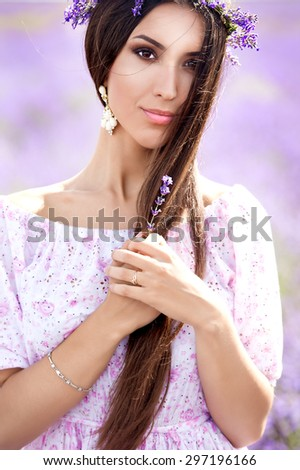 Beautiful girl with long dark hair in lavender wreath on the lavender field. Young woman with long hair collects lavender - stock photo