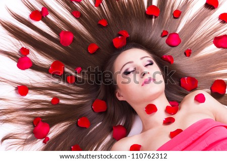 beautiful girl with long hair and flowers lying on white background - stock photo
