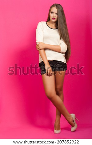 Beautiful girl with long hair in a fashionable clothes in the studio