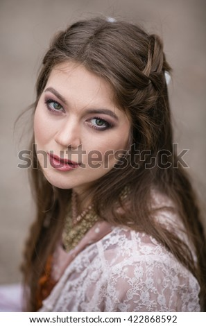 Beautiful girl with long hair in a pink vintage dress and long hear, closeup portraites
