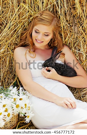 Beautiful girl with long hair on nature with a rabbit. Natural beauty.