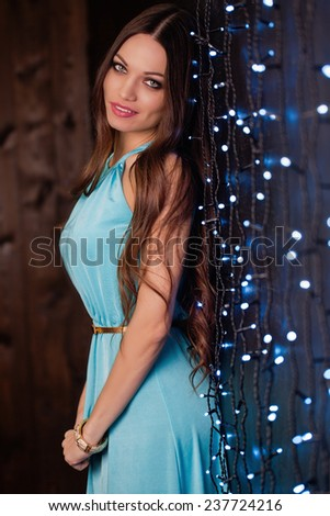 Beautiful girl with long hair portrait near led decorated wall - stock photo