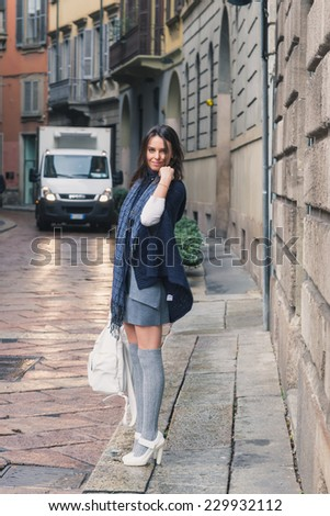 Beautiful girl with long hair posing in the city streets