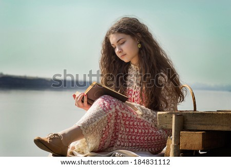beautiful girl with long hair reads the book at the river on the mooring. retro style - stock photo