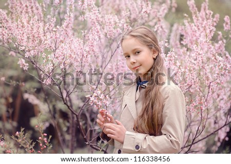 Beautiful girl with long hair standing in the spring park, near the bush with pink flowers - stock photo