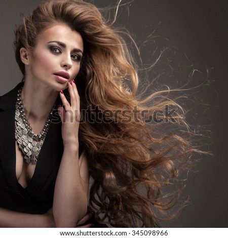 Beautiful girl with long healthy hair and glamour makeup looking at camera, wearing silver necklace. Studio beauty portrait.