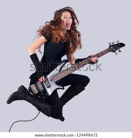 Beautiful girl with long red hair playing bass guitar and jumping in the air.