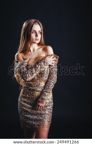 Beautiful girl with long straight blond hair. Fashion woman model posing at studio. Young cute smiling girl isolated on black background