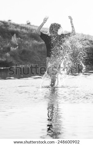 Beautiful girl with long, straight hair posing and playing with water in a small river. Black and white, artistic photography  - stock photo