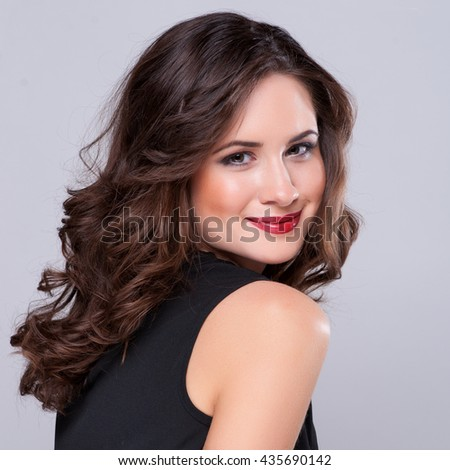 Beautiful girl with long wavy hair . Brunette model with curly hairstyle. - stock photo
