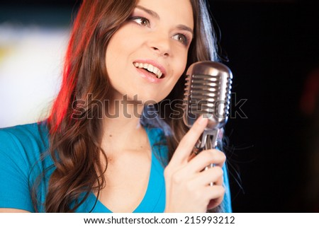Beautiful girl with microphone standing in bar. closeup of beautiful brunette girl singing with microphone.