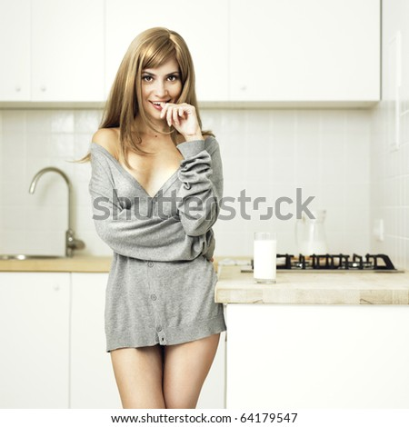 Beautiful girl with milk on the home kitchen - stock photo