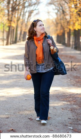 Beautiful girl with orange and baguettes walking in Parisian park
