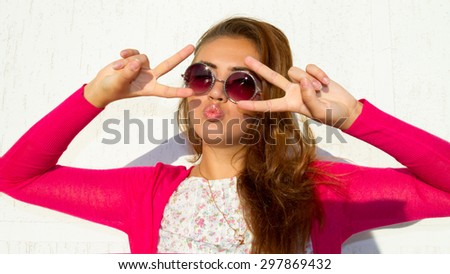 Beautiful girl with perfect hair, tan skin and pink lips wearing pink shirt and round pink retro sunglasses,send kiss, winking and smiling cause the summer party.Young trendy woman enjoying vacation