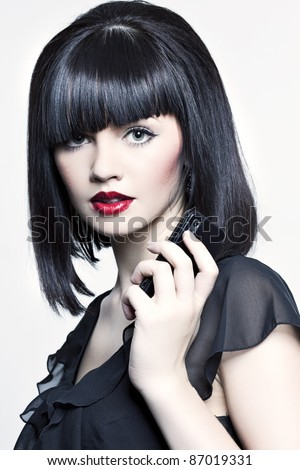 beautiful girl with perfect skin and bright red lipstick, black straight hair in the wind, developing, and with the phone in his hand on a white background - stock photo