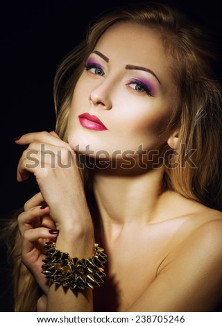 beautiful girl with perfect skin, blond hair and blue eyes posing on the black background. Close up portrait. interesting make up with purple color. Girl like rose concept - stock photo