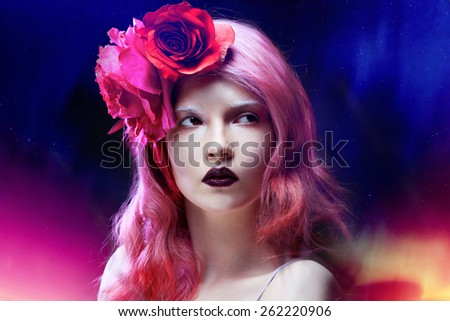 beautiful girl with pink hair on backdrop of the Northern lights - stock photo