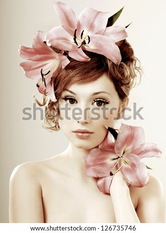 beautiful girl with pink lilies in her hair - stock photo
