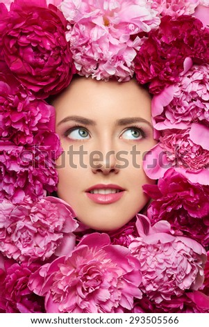 Beautiful girl with pink peony flowers. Closeup of beauty model woman face with perfect skin and professional makeup looking up - stock photo