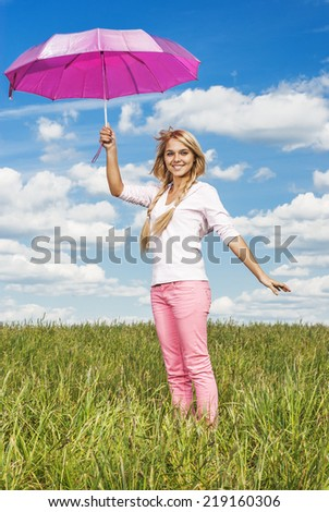 Beautiful girl with pink umbrella on summer green meadow. - stock photo