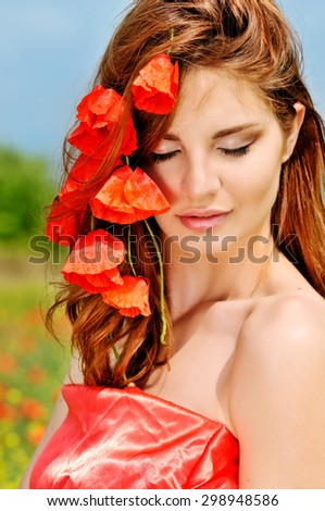 beautiful girl with poppies in red hair - stock photo