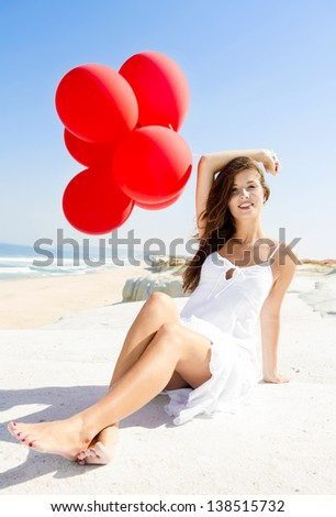 Beautiful girl with red ballons sitting in the beach - stock photo