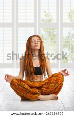 Beautiful girl with red dreadlocks meditating in pose of lotus - stock photo