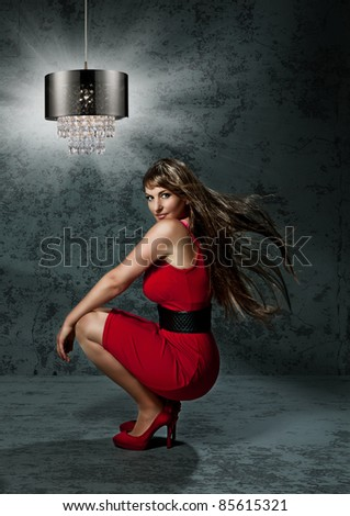 beautiful girl with red dress in front of an old wall - stock photo