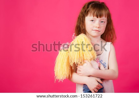 beautiful girl with red hair hugging her doll - stock photo