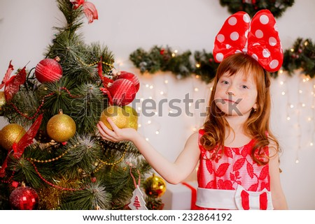 beautiful girl with red hair near the Christmas tree. Christmas toys and gifts - stock photo