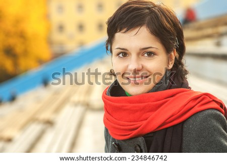 Beautiful girl with red scarf on autumn background. - stock photo