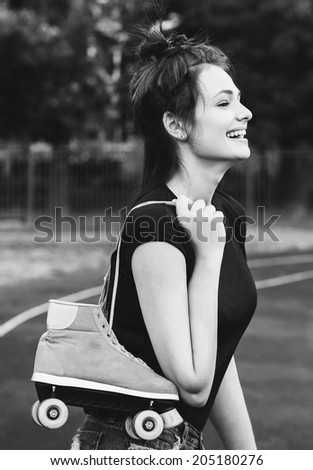 beautiful girl with roller skates on her shoulder walking in park, laughing and enjoy the moments. Outside - stock photo