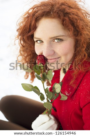 Beautiful girl with roses in the snow in winter