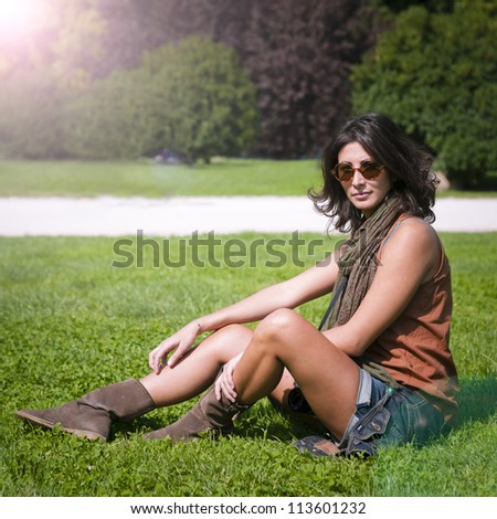 beautiful girl with scarf and sunglasses on the lawn in autumn