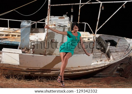 beautiful girl with sexy green dress and an old fishing boat on the background - stock photo