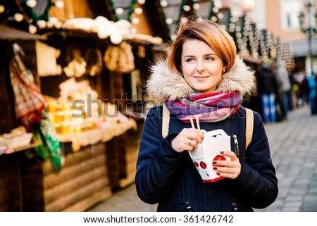 Beautiful girl with short red hair wearing winter jacket, in the street of European town holding chinese food and smiling, fest with Christmas decorations at the background, wearing dark red manicure - stock photo