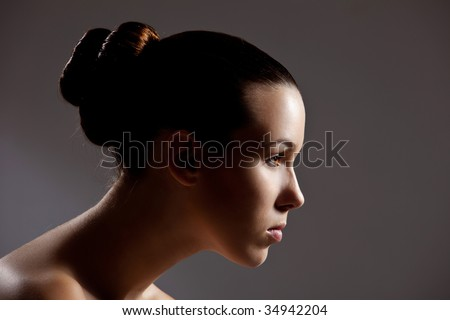 Beautiful girl with stylish hair in low key setting - stock photo