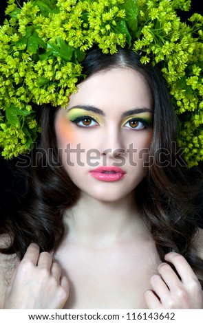 beautiful girl with stylish makeup and yellow- green flowers around her head