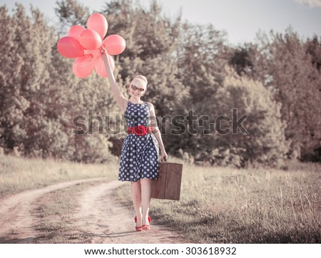 beautiful girl with suitcase and red balloons at countryside