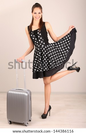 Beautiful girl with suitcase in room - stock photo