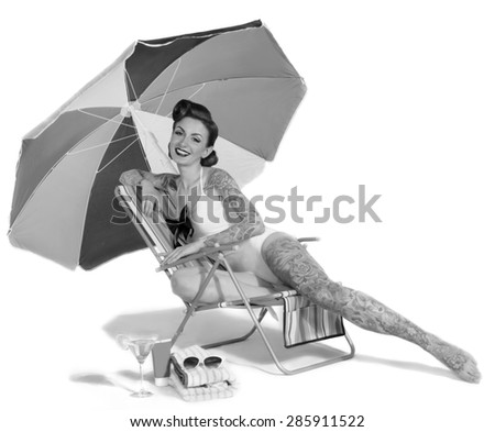 beautiful girl with tattoos sitting on the beach chairs retro style - stock photo
