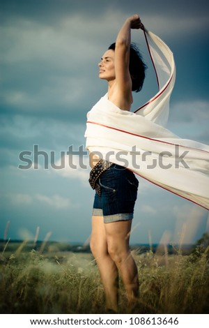 Beautiful girl with white scarf dancing  in a summer field against blue sky - stock photo