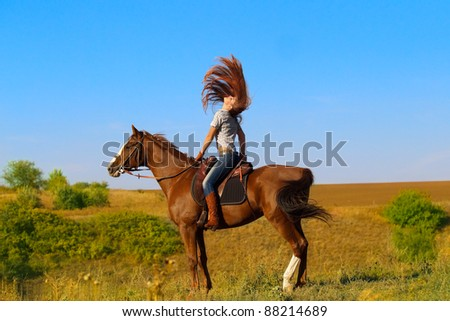 Beautiful girl with wind in her hair riding a horse in countryside