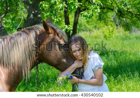 Beautiful girl with wreath of cornflowers in hands embraces muzzle of chestnut horse and laughs